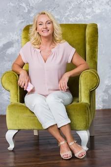 Senhora sorridente posando na cadeira verde