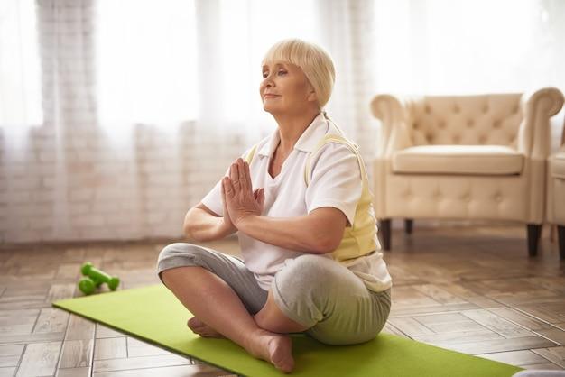 Senhora superior inspirada na ioga de relaxamento da pose dos lótus.
