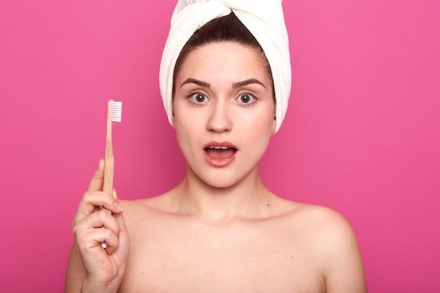 Senhora surpreendida com escova de dentes na mão, posando no banheiro enquanto escovar os dentes pela manhã, posa com ombros nus