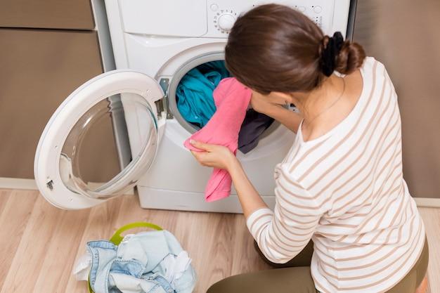 Senhora tirando a roupa na máquina de lavar roupa