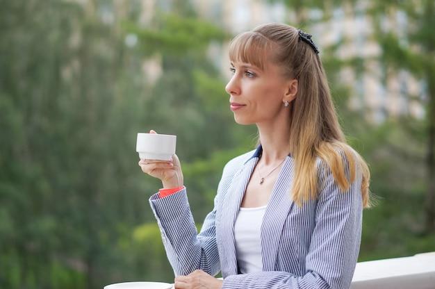 Senhora tomando café. uma xícara de café turco, segurando as mãos das mulheres.