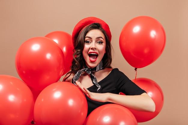 Senhora travessa de olhos verdes com lábios vermelhos grita com alegria, olha para a câmera e posa em fundo bege com balões.