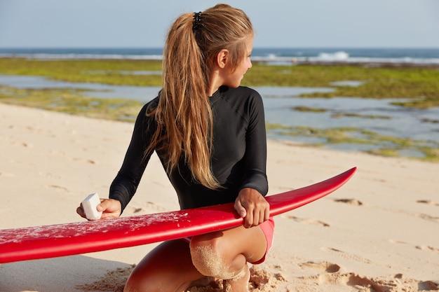Senhora vestida com cauda de castor, se prepara para a sessão de surf, segura a cera e a prancha de surf