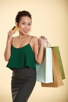 Senhora vietnamita sorridente posando com cartão de crédito e sacolas de compras