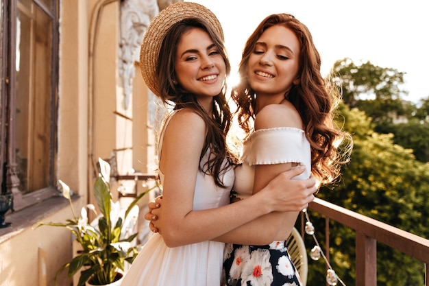 Senhoras adoráveis de bom humor se abraçando em uma grande varanda