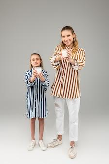 Senhoras agradáveis e sorridentes em camisas listradas de cores vivas, com copos cheios de leite nas mãos