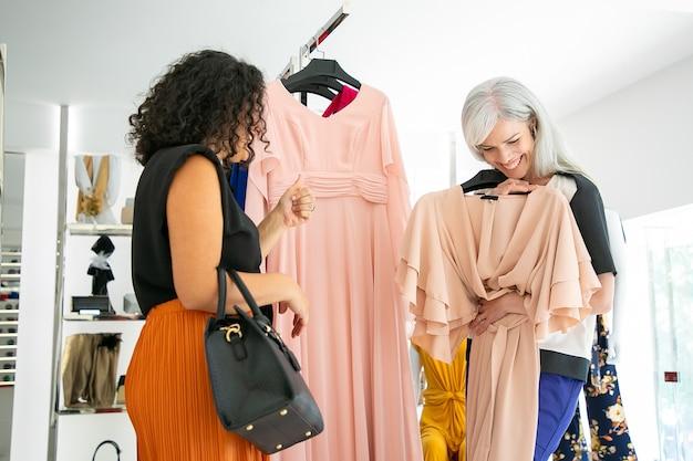 Senhoras alegres escolhendo roupas novas em loja de moda juntas, segurando um vestido de festa com cabide, conversando e rindo. consumismo ou conceito de compras