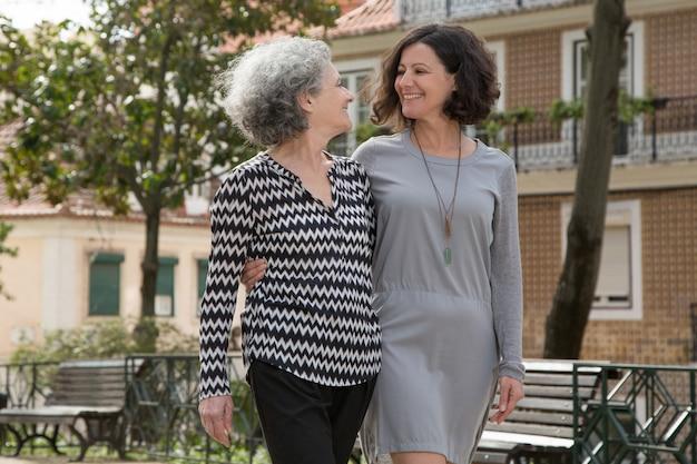 Senhoras alegres jovens e seniores caminhando ao ar livre