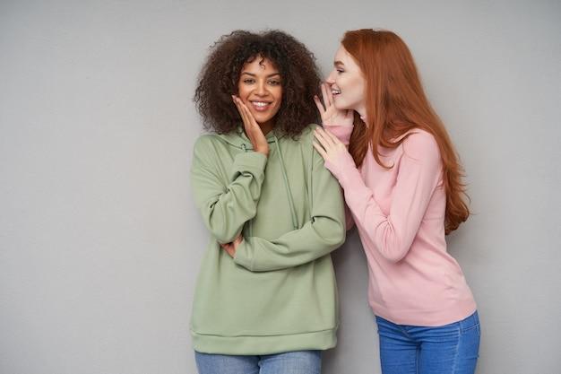 Senhoras atraentes vestidas com roupas casuais, compartilhando novidades emocionantes e sorrindo positivamente enquanto ficam de pé contra a parede cinza