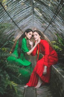 Senhoras bonitas em vestidos posando em uma casa verde