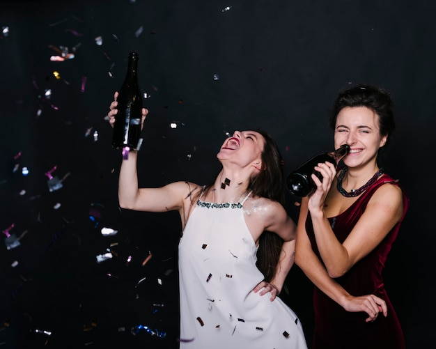 Senhoras chorando em vestido de noite com garrafas de bebidas entre jogando confete