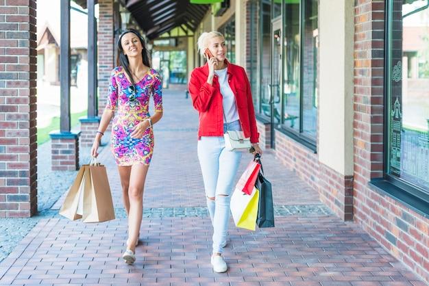 Senhoras, com, bolsas para compras, ir, ligado, rua comercial
