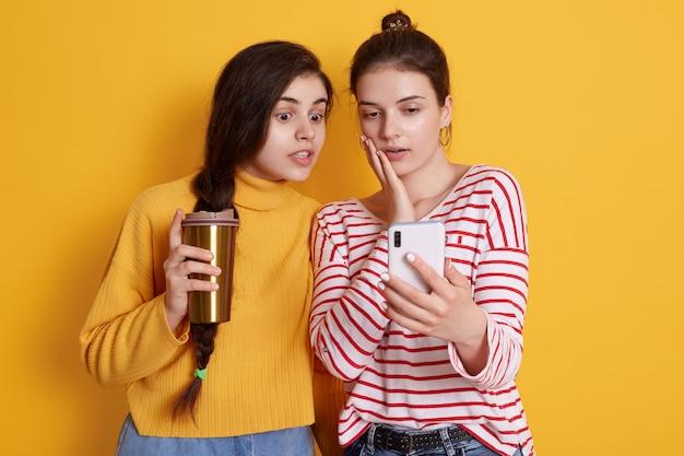 Senhoras com telefone inteligente nas mãos e tirar café