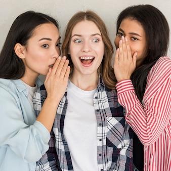 Senhoras compartilhando um segredo chocante para se divertir