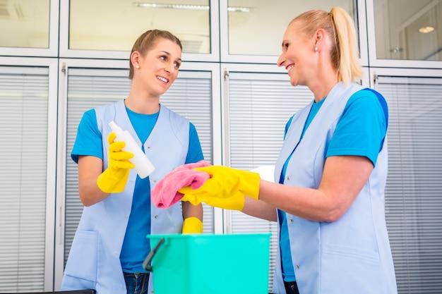 Senhoras da equipe de limpeza comercial trabalhando em equipe no escritório