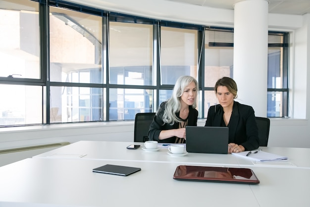 Senhoras de negócios sérios assistindo e discutindo o conteúdo do laptop enquanto está sentado à mesa com xícaras de café na sala de reuniões. tiro amplo. trabalho em equipe e conceito de comunicação