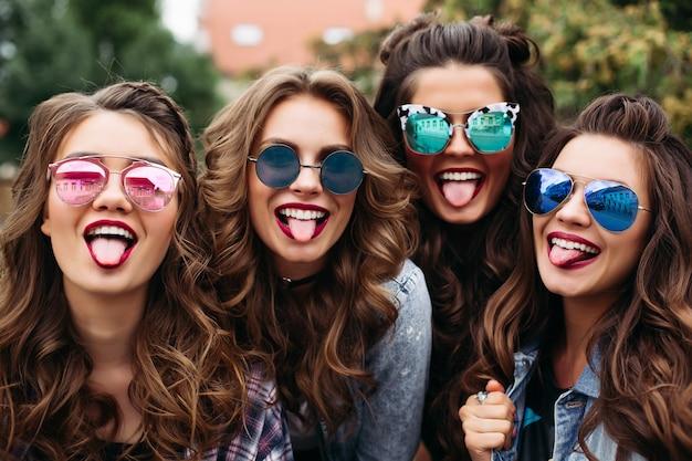 Senhoras elegantes com penteado tomando selfie ao ar livre.