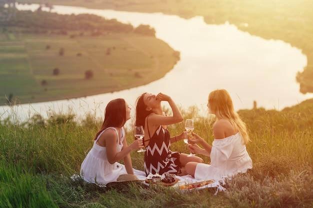 Senhoras elegantes e elegantes bebendo vinho e comendo frutas frescas enquanto está sentado na colina no piquenique ao pôr do sol.
