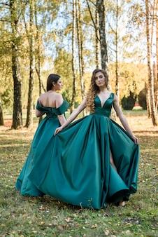 Senhoras em elegantes vestidos verdes, caminhando no parque outono. menina morena garotas sonhadoras rindo ao ar livre