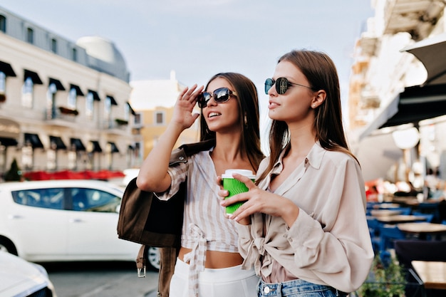 Senhoras rindo encantadoras posando juntas no fundo da cidade.