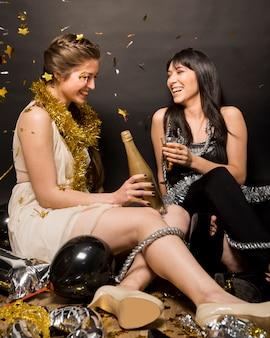Senhoras rindo no desgaste da noite com copo de bebida e garrafa no chão