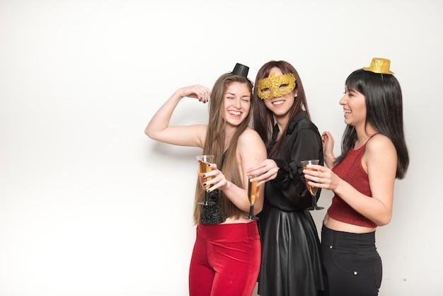 Senhoras rindo no desgaste da noite com copos de bebidas
