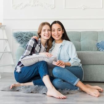 Senhoras sentadas abraçando no chão descalço com travesseiro e telefone celular