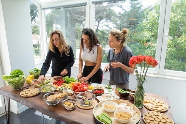 Senhoras sérias cozinhar e cortar legumes na cozinha