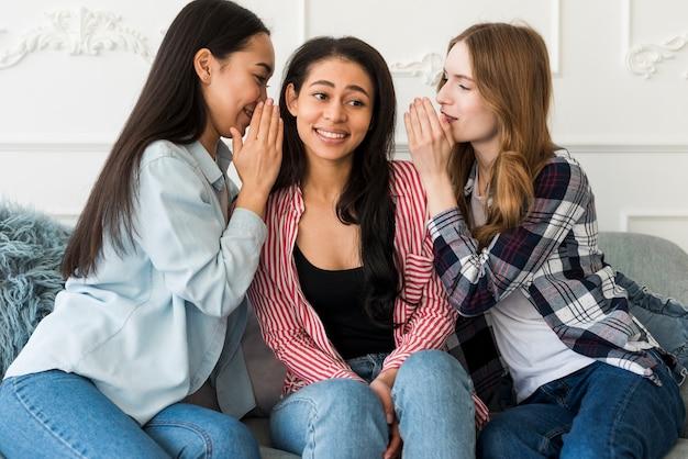Senhoras sussurrando em segredo de orelha de amigos