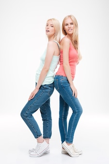 Senhoras vestidas com camisetas e jeans posando. isolado sobre parede branca