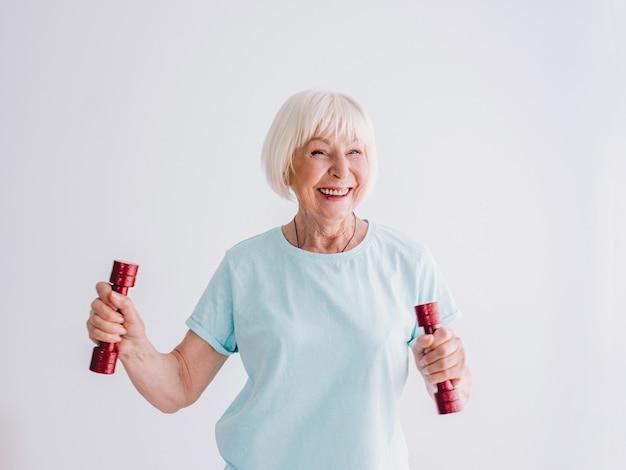 Sênior alegre mulher praticando esportes com halteres anti-idade esportes estilo de vida saudável