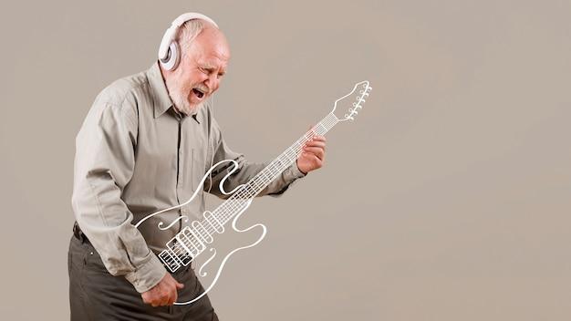 Senior animado tocando guitarra imaginária