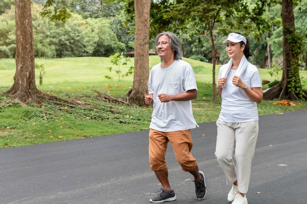 Sênior asiático ativo casal no sportswear, movimentando-se no parque.