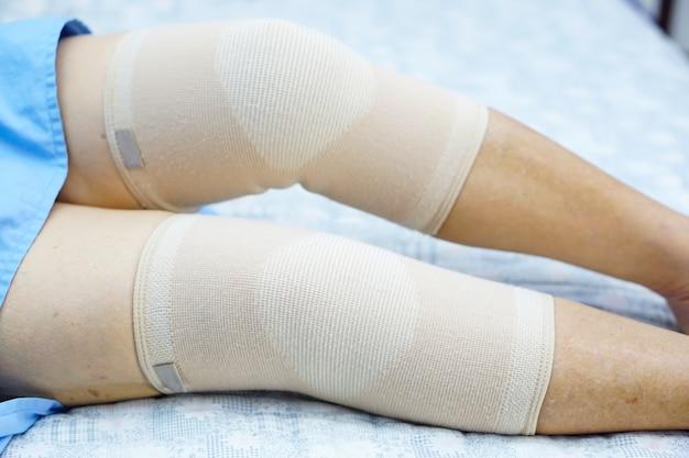 Sênior asiático ou paciente idoso da mulher da senhora idosa com junção da dor do apoio do joelho.