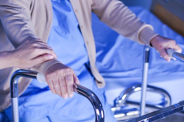 Sênior asiático ou paciente idoso da mulher da senhora idosa com o caminhante que senta-se na cama.