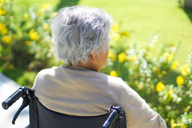 Sênior asiático ou paciente idoso da mulher da senhora idosa na cadeira de rodas no parque.