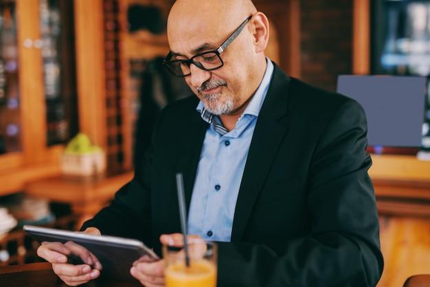 Senior barbudo de terno usando tablet enquanto está sentado na cafeteria.