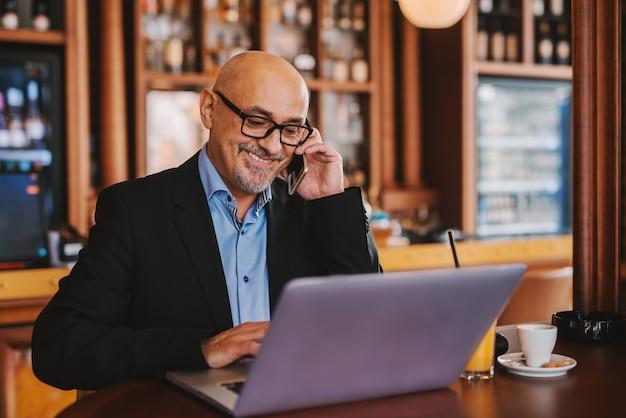 Senior barbudo de terno usando telefone inteligente e laptop enquanto está sentado na cafeteria.