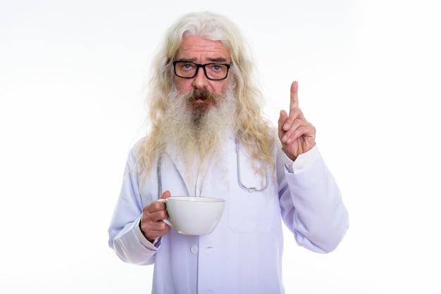 Sênior barbudo médico segurando uma xícara de café