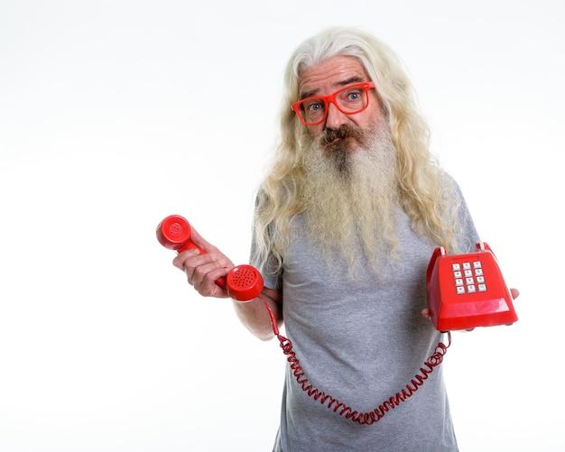 Sênior barbudo parecendo confuso segurando um telefone antigo