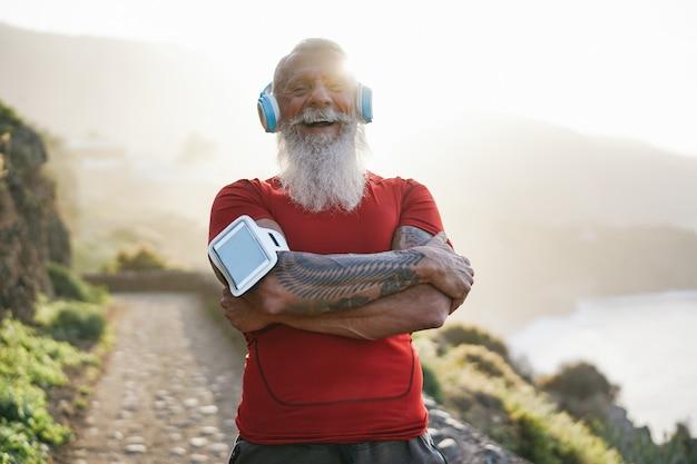 Senior cabe homem ao ar livre ao pôr do sol após a sessão de treino - atleta maduro treinamento fora enquanto ouve música da lista de reprodução com fones de ouvido