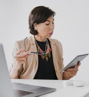 Sênior com colar segurando um tablet