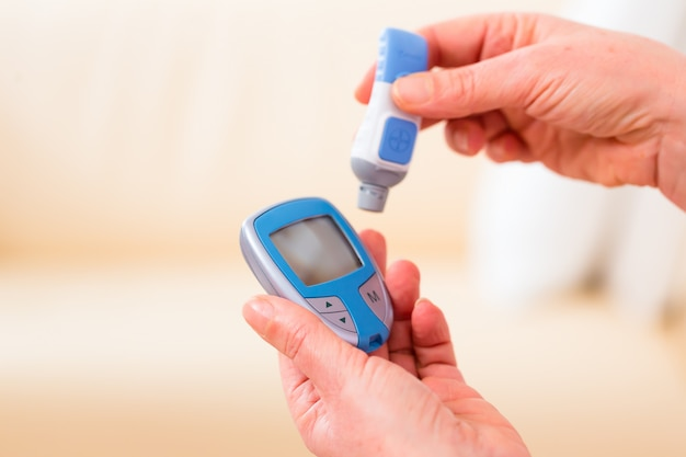 Senior com diabetes usando analisador de glicose no sangue
