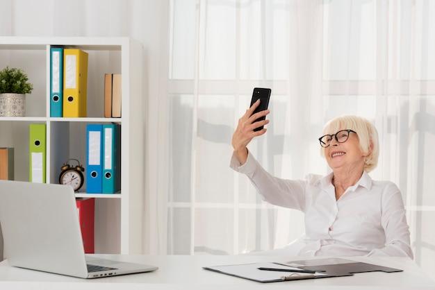 Sênior com óculos, segurando o telefone