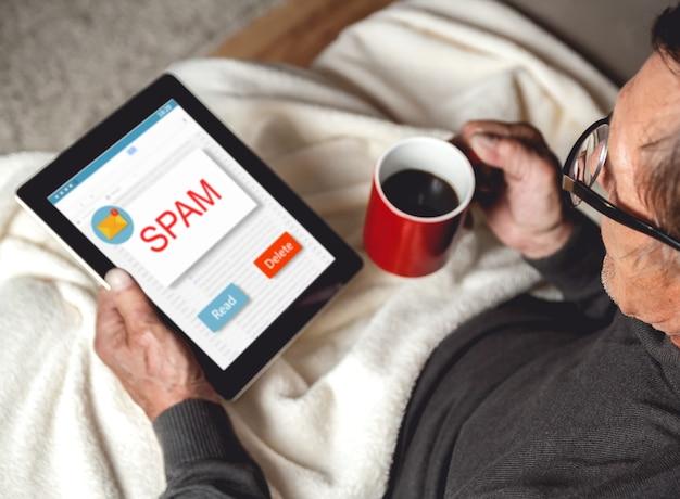 Sênior com óculos sentado no sofá com um tablet e uma xícara vermelha de café nas mãos.