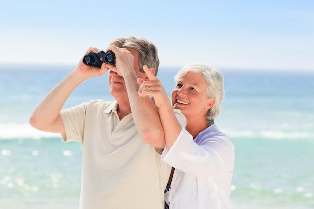 Senior couple bird watching in the beach