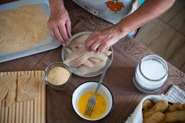 Sênior cozinhando em casa sozinho pescar com amor e paixão - aposentada, madura e cozinheira interna dos anos 60 - mãos pegando peixes
