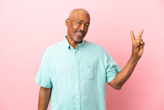 Sênior cubano isolado em fundo rosa sorrindo e mostrando sinal de vitória