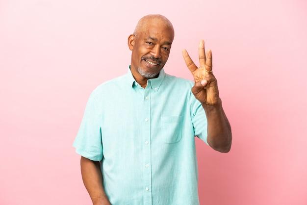 Sênior cubano isolado em um fundo rosa feliz e contando três com os dedos