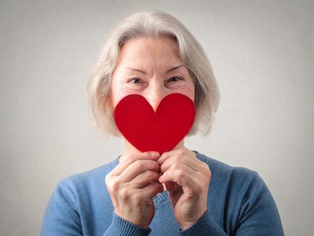 Senior dama segurando um coração de papel